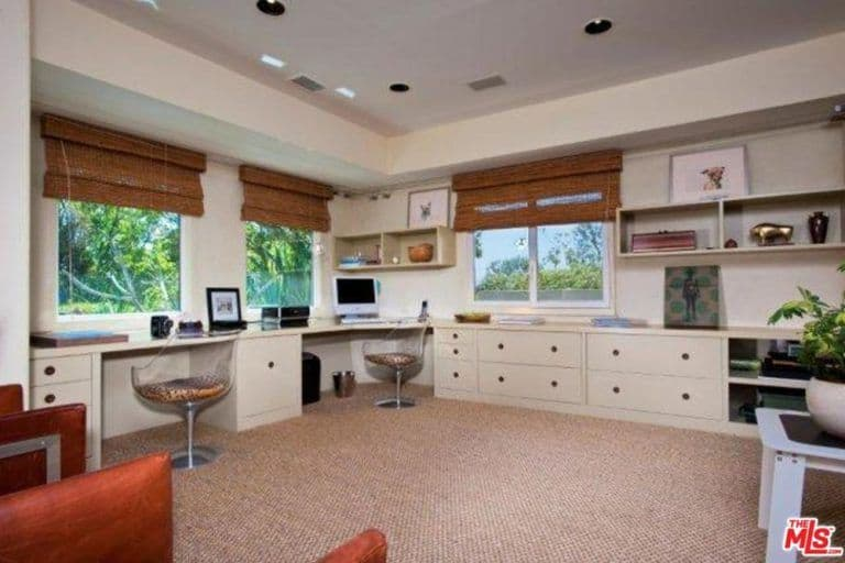 The Home Office Has Two Built In Desks And Multiple Cabinets Along With  Glass Windows