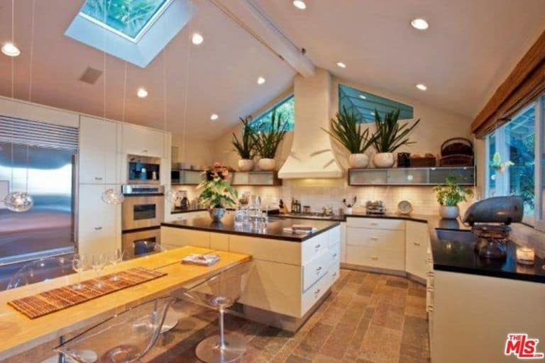 Large kitchen set with a stylish dining table and glass seats set on the hardwood flooring. The high vaulted ceiling also attracts attention because of its lighting.