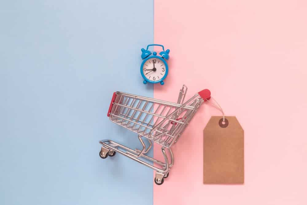 Shopping cart with a price tag attached and an alarm clock on top against a pastel backdrop.
