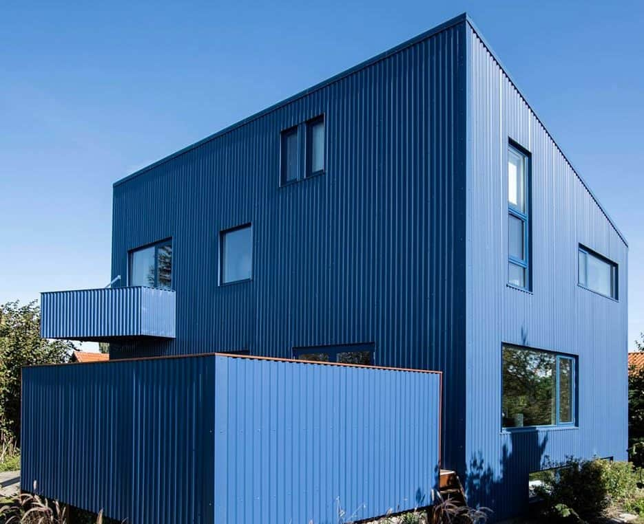 This is an exterior view of the modern house with blue textured exterior walls complemented by the small windows and unique design.