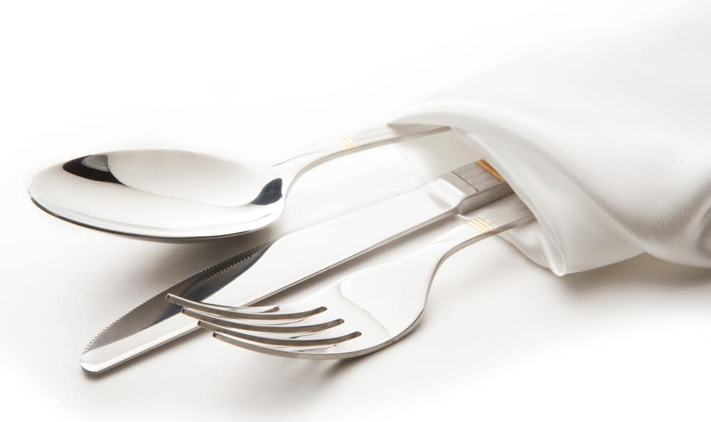 Cutlery set of spoon, knife and fork wrapped in a white cloth napkin.