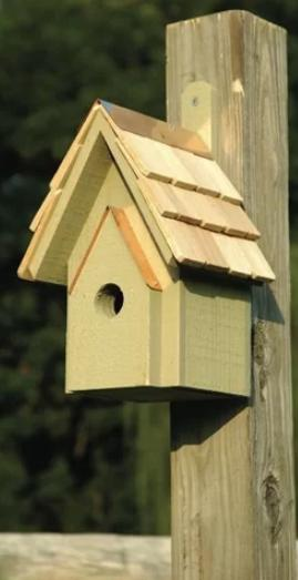Small, wooden birdhouse with a copper roof.