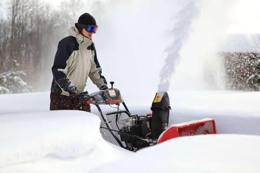 A woman using a snow blower during winter.