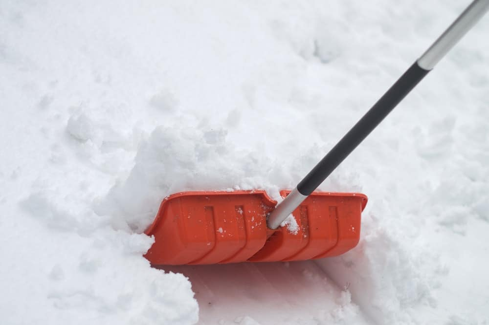 Red snow shovel scooping up mounds of snow.