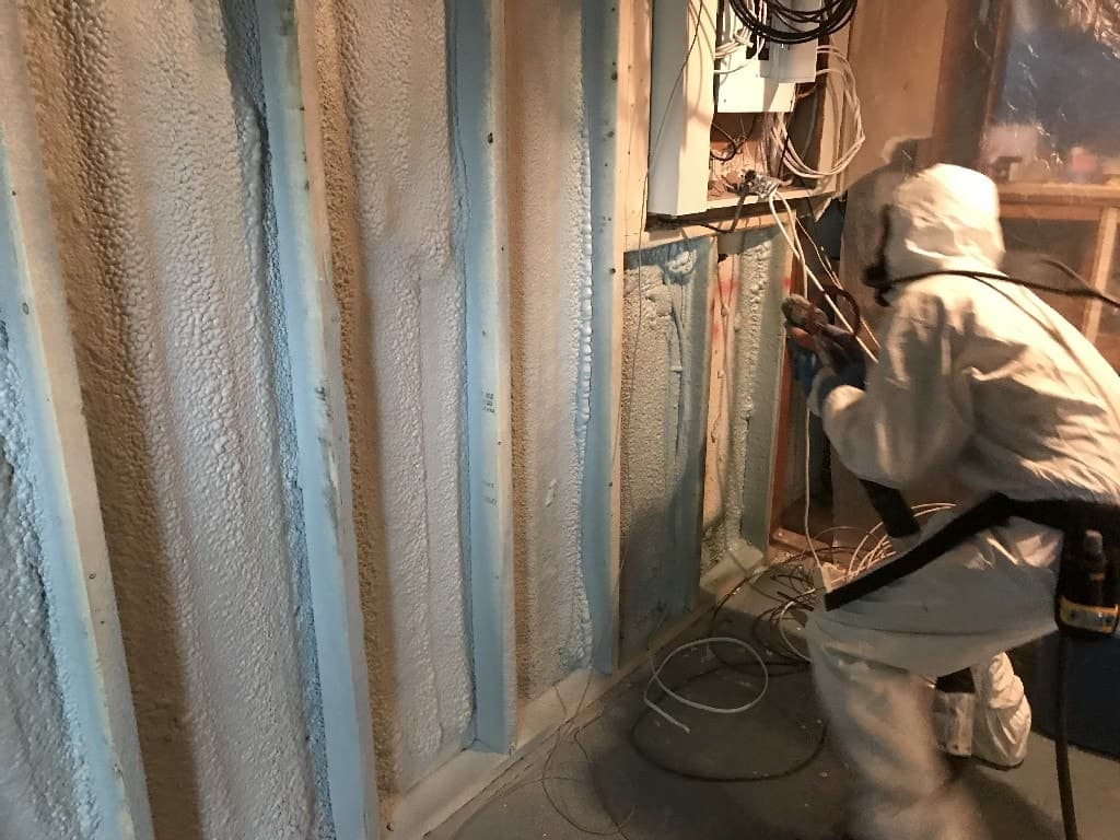 Man spraying spray foam insulation in between wall studs to insulate the basement wall
