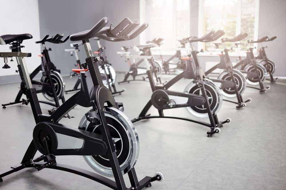 Empty stationary bikes in a fitness gym.