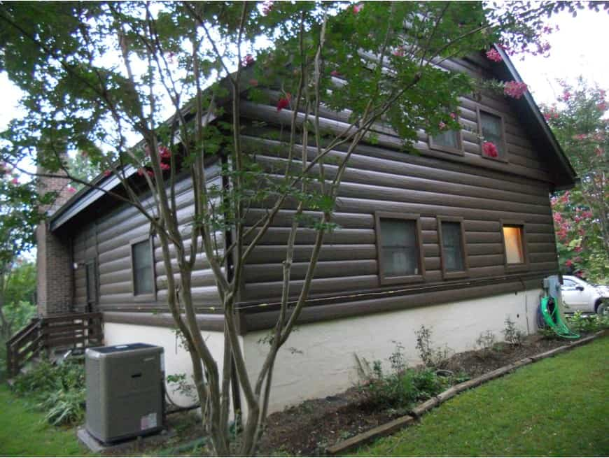 An outdoor view of a brown house focusing on its steel log siding.