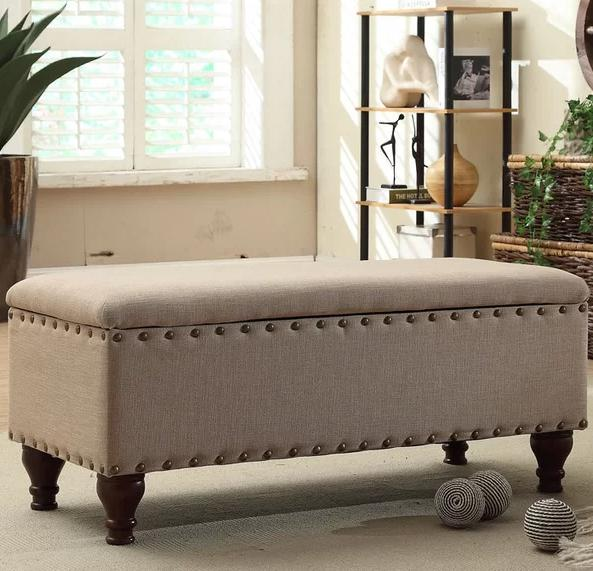An upholstered, bench storage trunk in Tan.