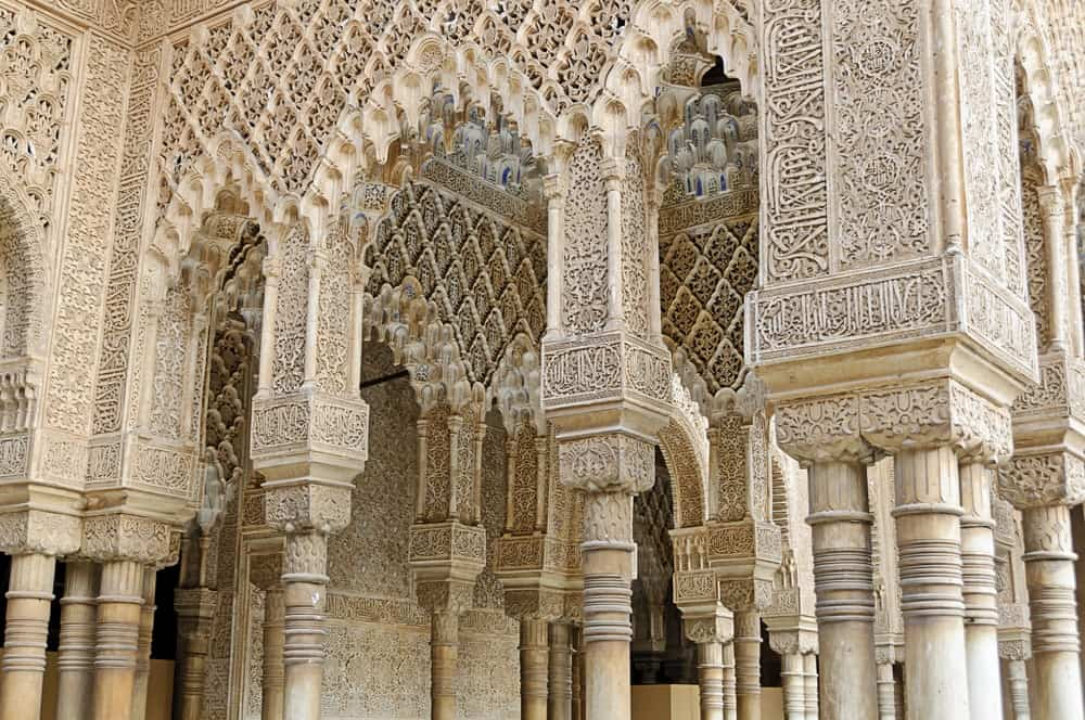 """Decorated arches and columns in the """"Patio de los Leones"""" inside Nasrid Palace or Palacio Nazaries in the complex of the Alhambra, Granada, Spain."""