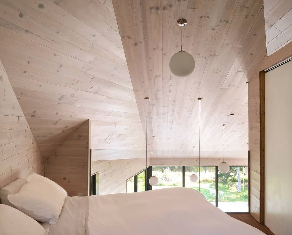The bedroom is surrounded by hardwood walls and ceiling and offers a comfortable bed. Photo credit: Louis Prud'homme