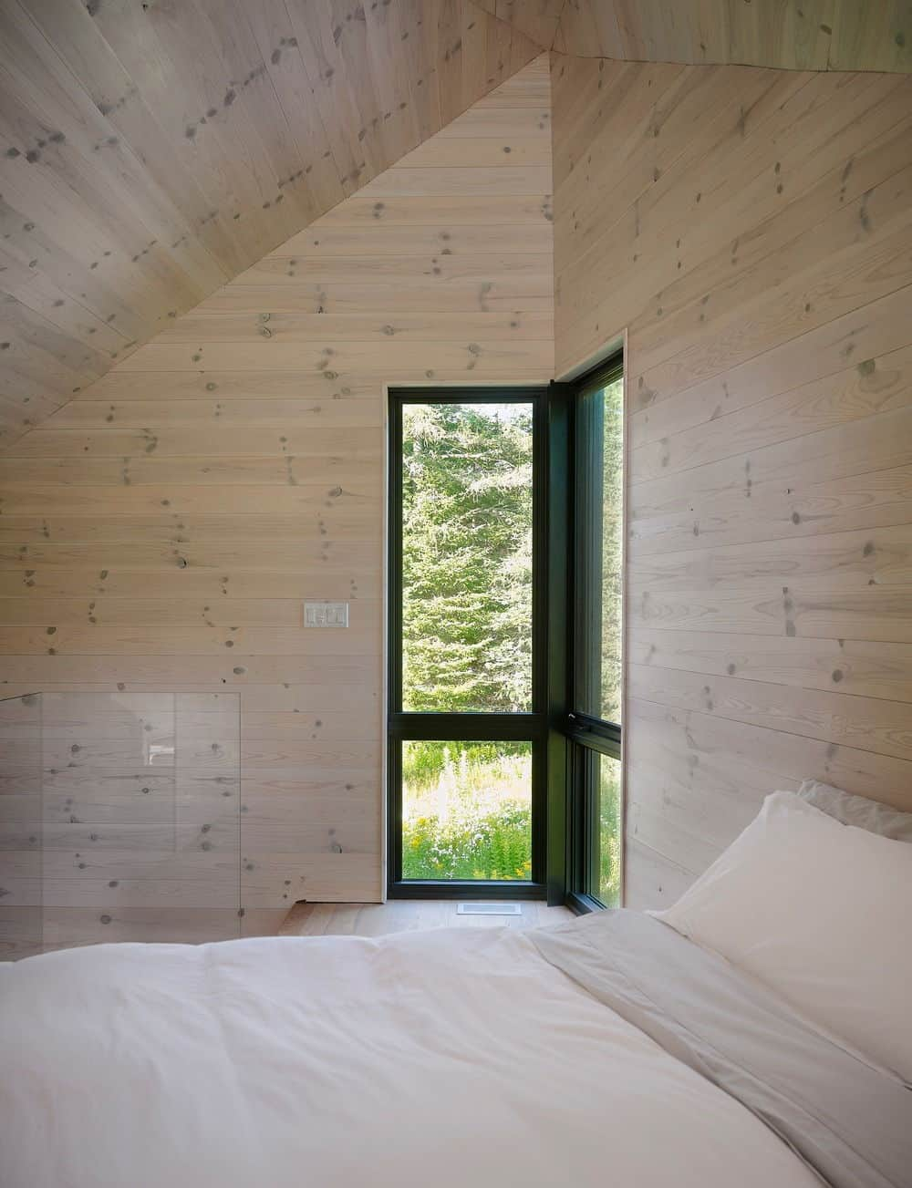 Another look of the bedroom featuring the hardwood walls and a glass corner window. Photo credit: Louis Prud'homme