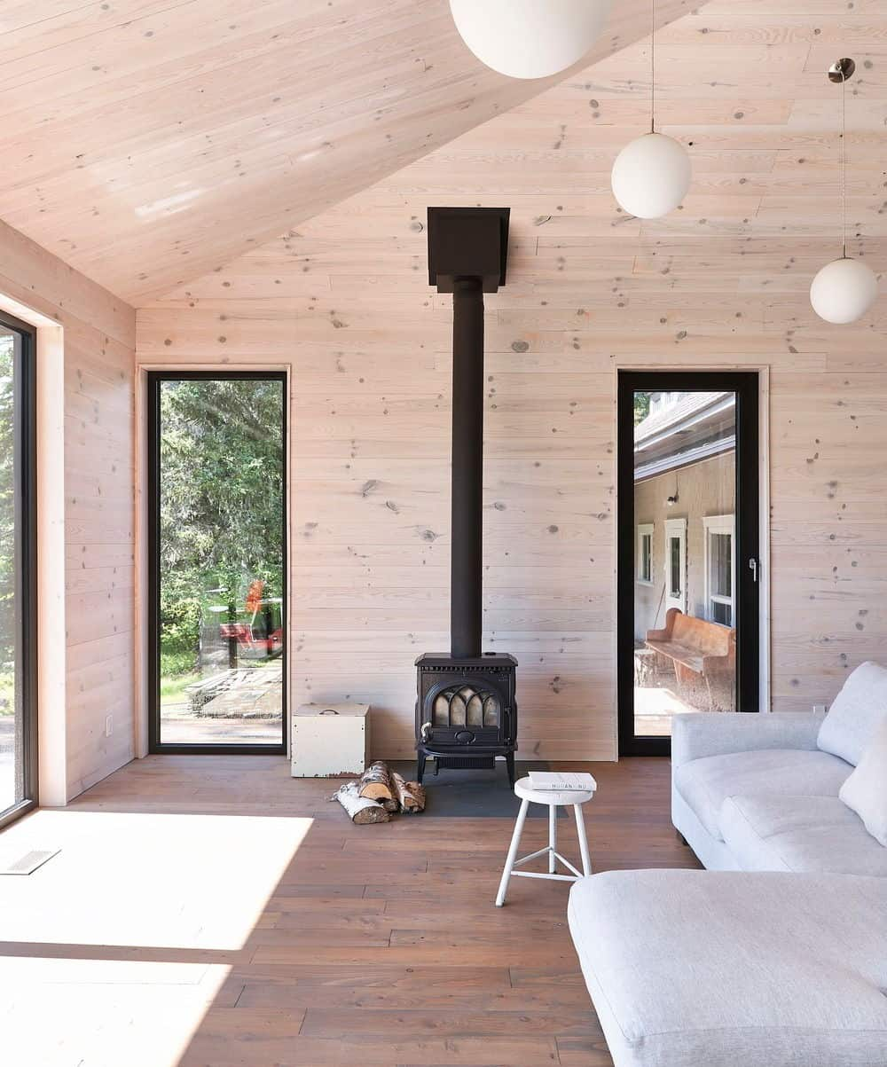 The living room offers a comfy couch with a fireplace and glass doors leading to outdoor amenities. Photo credit:Louis Prud'homme