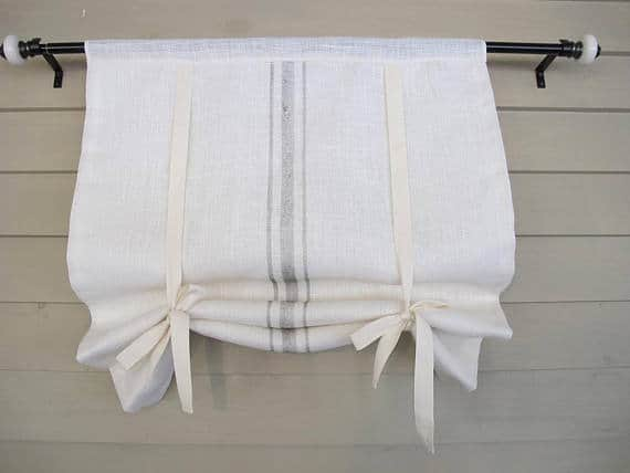 This white burlap window shade is embellished with painted stripes that mimic the woven stripes of old French textiles.