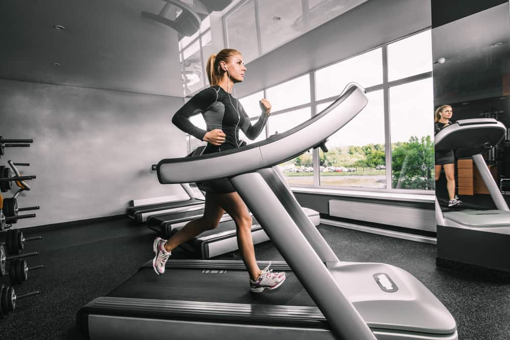 Woman running on treadmill in a fitness gym.