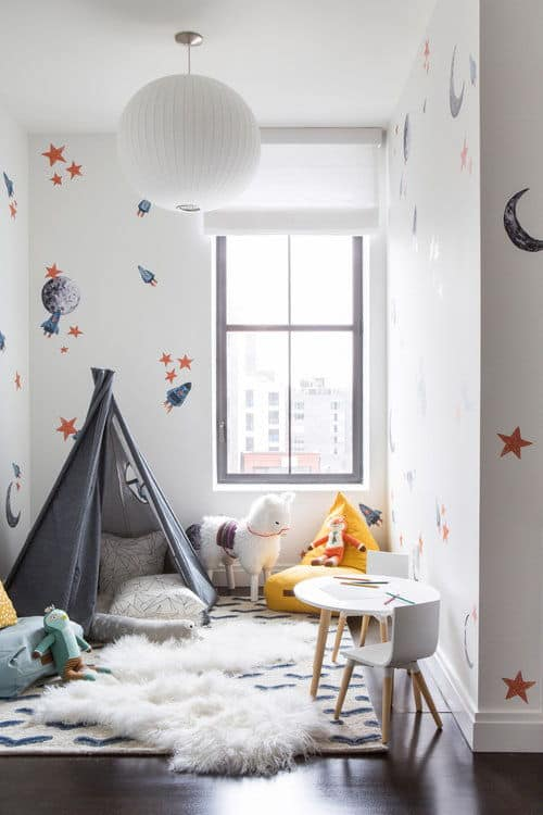 Another kids room featuring stylish walls and hardwood flooring along with a playing area. Photo Credit: Sarah Elliot