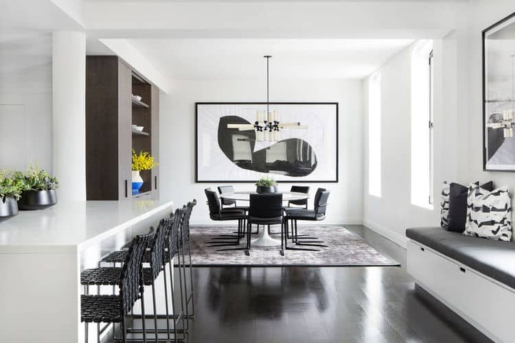 Black and white kitchen decorated with a minimalist wall art mounted across the dining set that sits on a gray rug. It has a window seat nook and peninsula lined with black woven counter chairs.