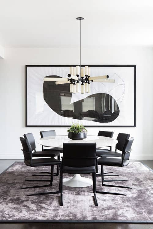 Contemporary dining room decorated with black framed wall art and a unique chandelier that hangs over the white round dining table contrasted with black leather chairs.
