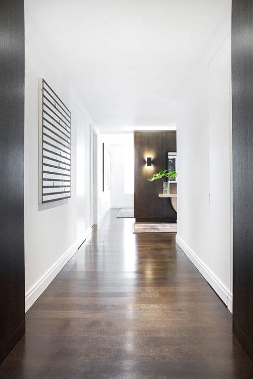 The home's entry features a hardwood flooring and white walls. Photo Credit: Sarah Elliot
