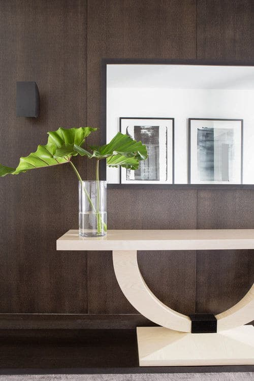 The entry features a contemporary console table and a mirror with wall decors. Photo Credit: Sarah Elliot