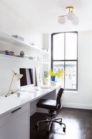 This her's home office features a smooth white desk with shelves along with a table lamp. Photo Credit: Sarah Elliot