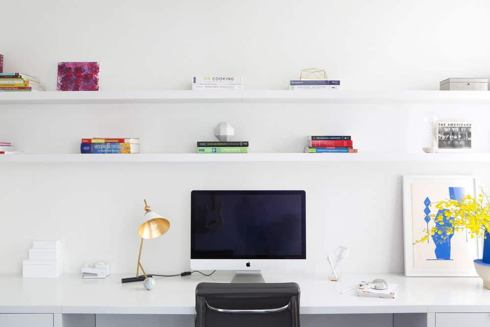 Another look of the her's home office featuring its white walls, desk and shelves. Photo Credit: Sarah Elliot