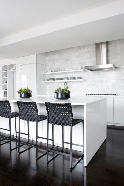 Black wicker counter chairs sit at a breakfast island in this kitchen with white fridge and stainless steel vent hood mounted on the gray subway tile backsplash.