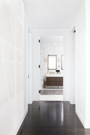 A hallway leading to the primary bathroom featuring a hardwood floors and white walls. Photo Credit: Sarah Elliot