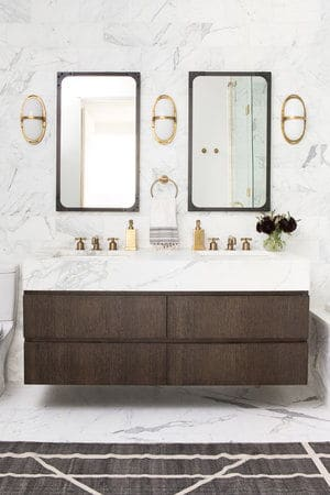 A close up look at this primary bathroom's stylish floating vanity double sink surrounded by marble tiles walls and floors.