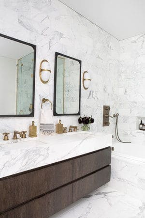 The bathroom features elegant marble walls, flooring and sink countertop, along with a soaking tub. Photo Credit: Sarah Elliot