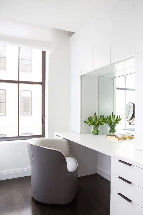 This is the her's dressing room near the closet featuring a smooth white desk and walls. Photo Credit: Sarah Elliot