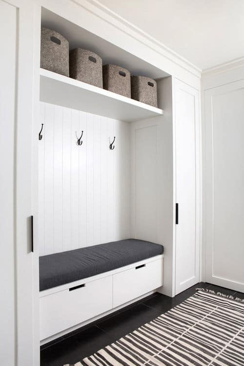 The house's mudroom features a rug on top of the espresso flooring along with white walls. Photo Credit: Sarah Elliot