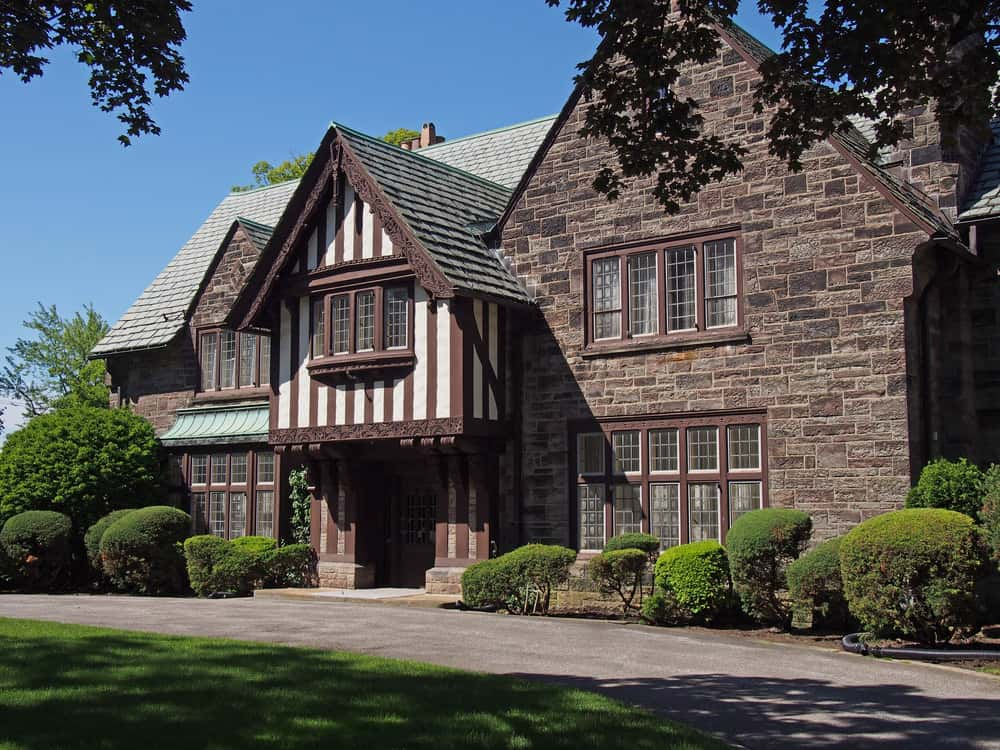 Extensive gray brick with some classic half-timbering form the exterior of this Tudor style home. Notice the jettied upper flor over the entrance which is another hallmark of the Tudor style.