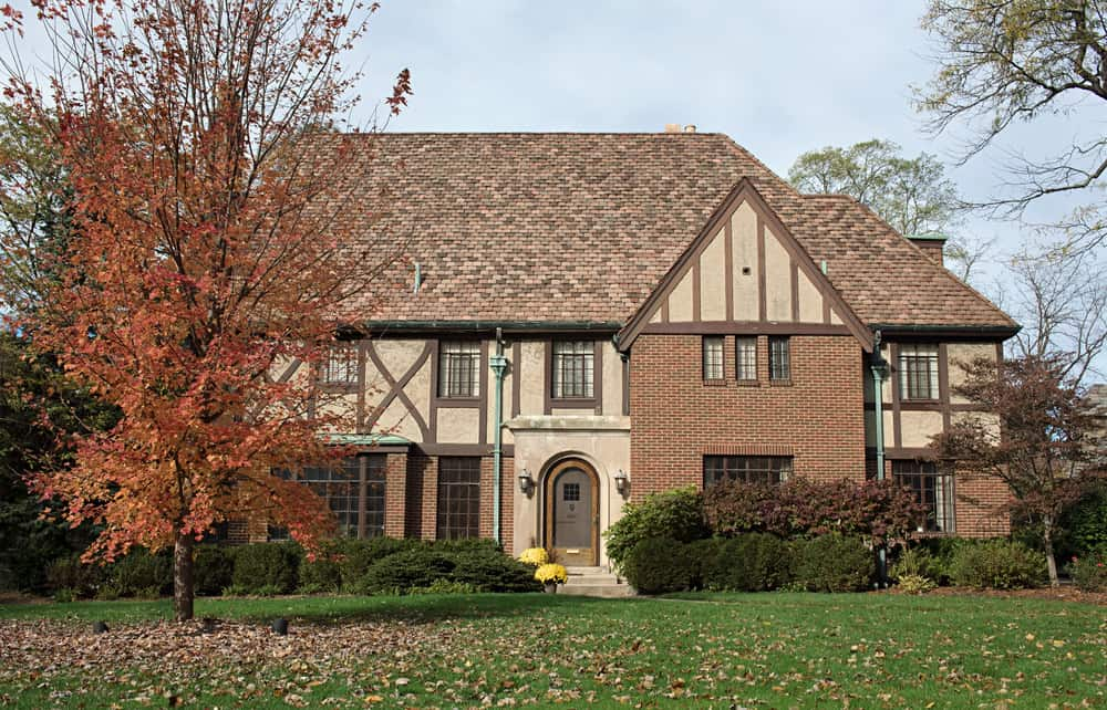 This Tudor style home is relatively newly built (i.e. not built in the 19th Century) and is different in that it features brown half-timbering on a light brown exterior. Normally it's dark brown or black on white. Nevertheless, the timbering and steep roof along with brick exterior result in a Tudor style home.