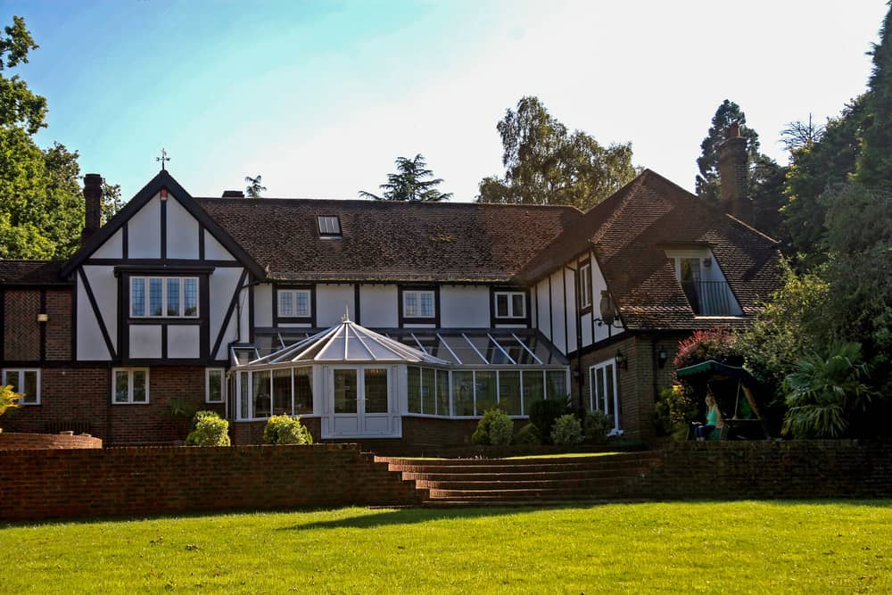 Here's the rear of a newer Tudor style home with large solarium looking out onto a large lawn. The first floor exterior is brick and the upper floors have the classic half-timbering on white. The rear design is rather simple in that it lacks the depth that many front facades of Tudor homes enjoy.