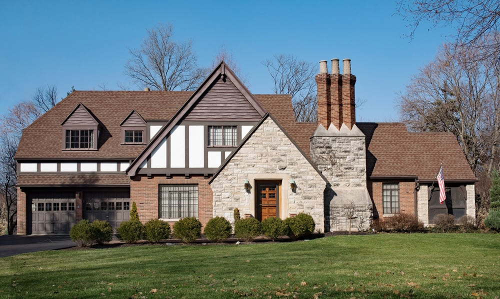 Here's a classic suburban Tudor style home putting in a decent effort to replicate the 19th century Tudor revival style except I think going with three exterior materials is a mistake. It could be improved sticking with just red brick and half-timbering on white.