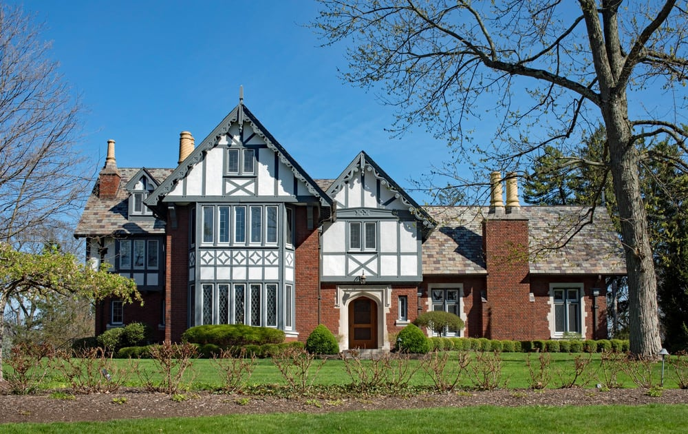 Definitely Tudor in style but I'm not fond of the gray half-timbering or the ornamental eaves. Black or dark brown timbering would fit much better with the red brick facade. I do like, however, the large jutting fron bay windows for both the upper and lower floor.