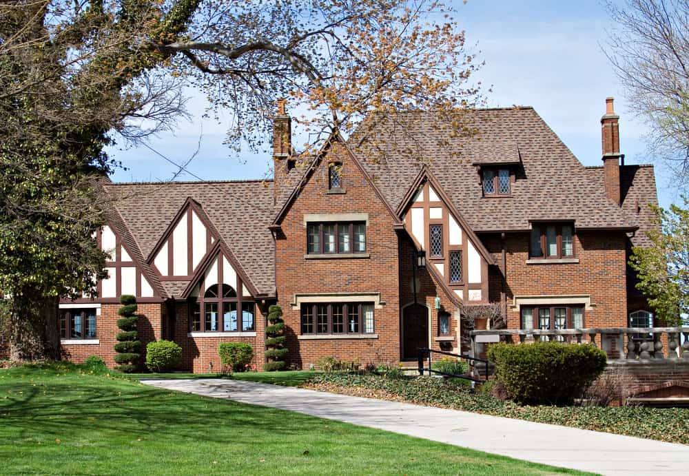 Contemporary Tudor Revival style home with brown half-timbering on white as well as red brick exterior. Steep roof and tall chimneys on each side of the main structure.