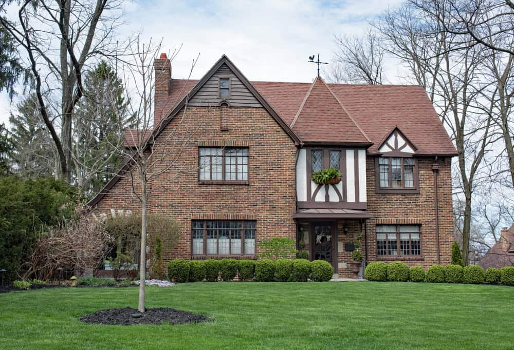 I like this take on a contemporary Tudor build. While mostly brick on the outside, you get a smidgen of half-timbering which acts as an accent design element along with the steep roof lines gives it the Tudor look.