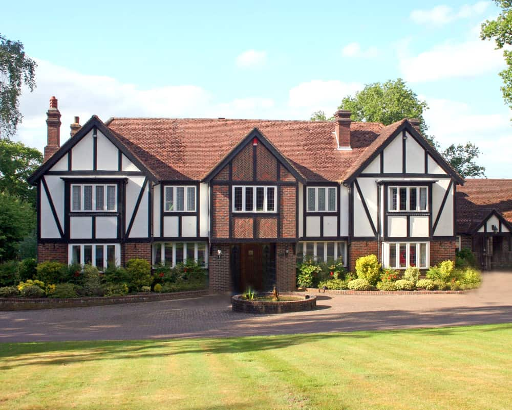 Fairly simply symmetric Tudor style home. It lacks the steep roof lines other Tudor homes have which doesn't make it as grand as it could be, but the half timbering and brick exterior facade give it a Tudor appearance.