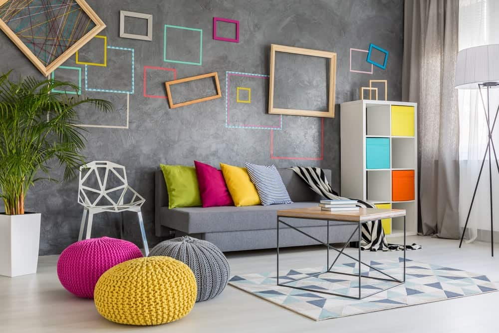 Stylish living room featuring geometric accents from the grey wall with multiple square and rectangular frames and bright-colored accent pieces.