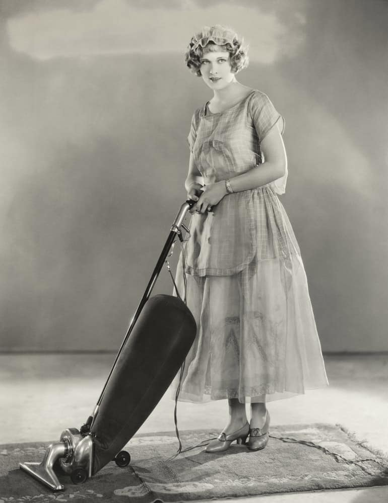 Lady from a previous era holding one of the earliest versions of a vacuum cleaner.