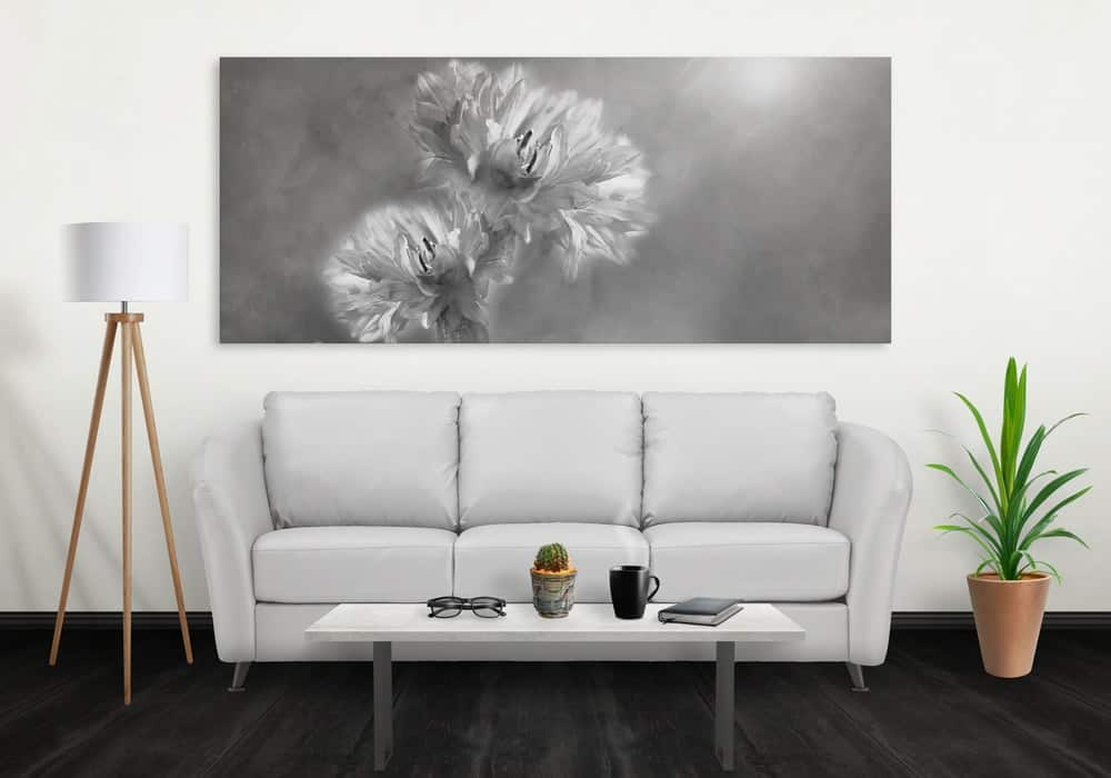 Floral wall art canvas on a gray scale displayed above the white sofa in a modern living room.