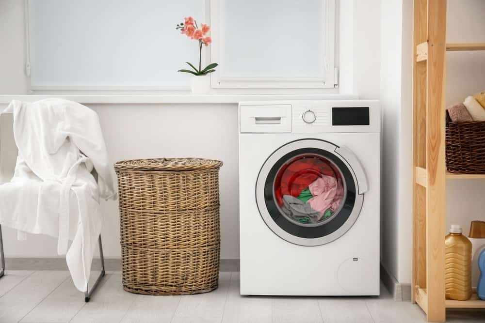 Laundry in washing machine and basket in laundry room.
