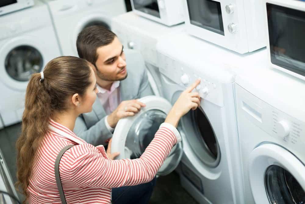 Happy young couple choosing washing machine in hypermarket.