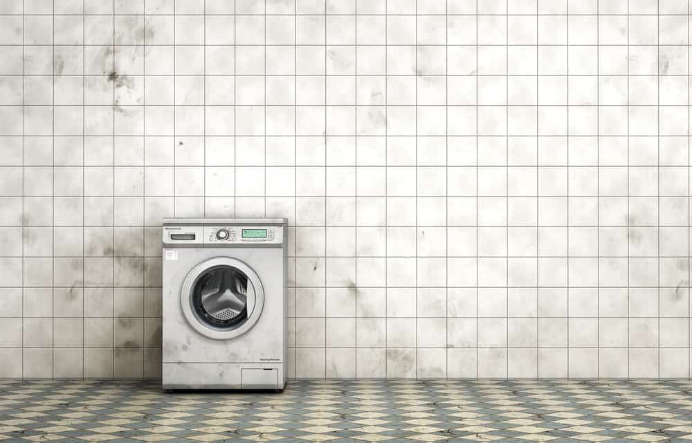 Dirty washing machine in the empty dirty tiled room in grunge style.