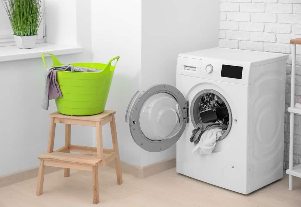 Basket with laundry on stool and washing machine in a bathroom.