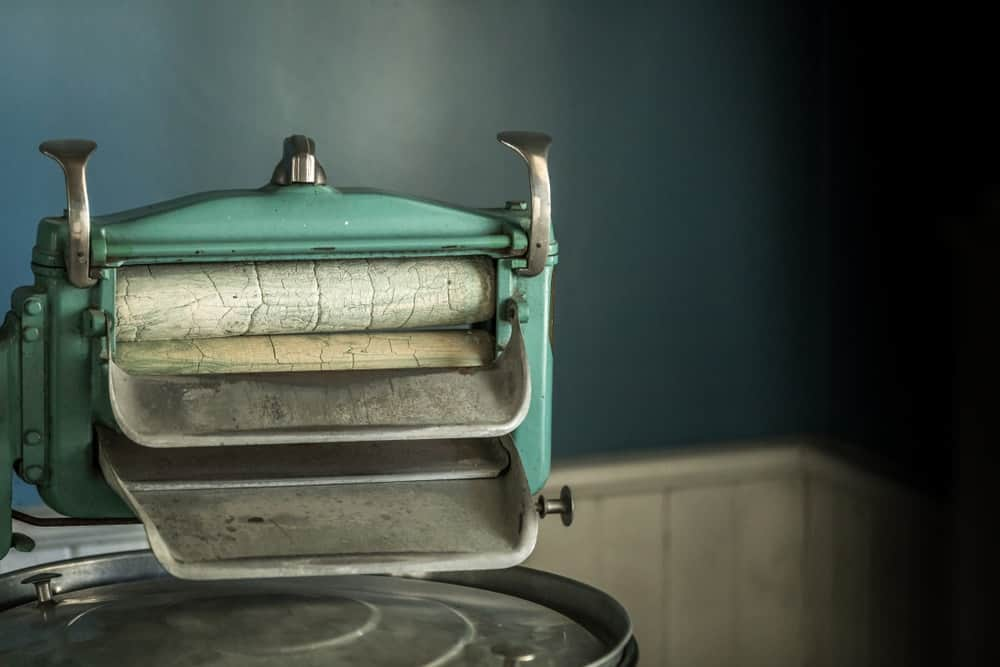 A turquoise vintage washing machine wringer in a room.