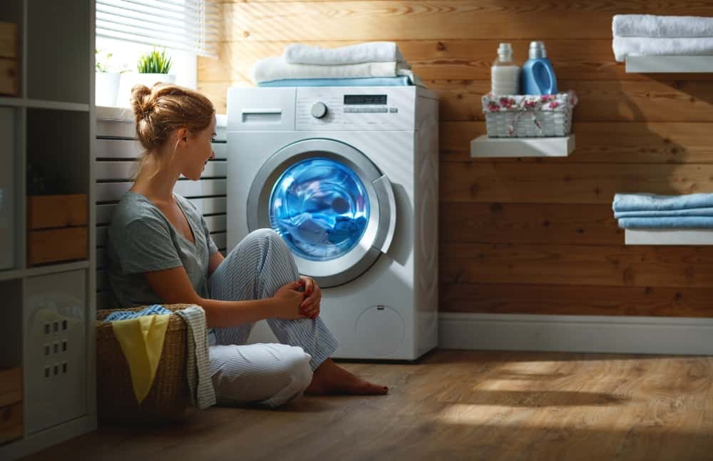Happy housewife in laundry room with washing machine.