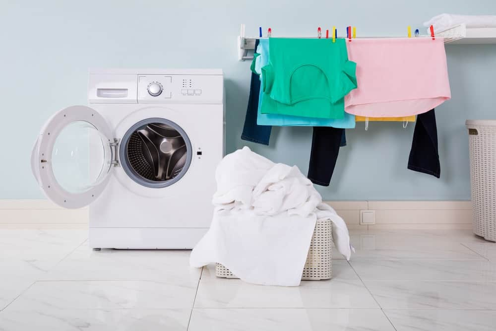 Clean clothes hang on a drying rack and a basket of white towels beside an empty and open washing machine.