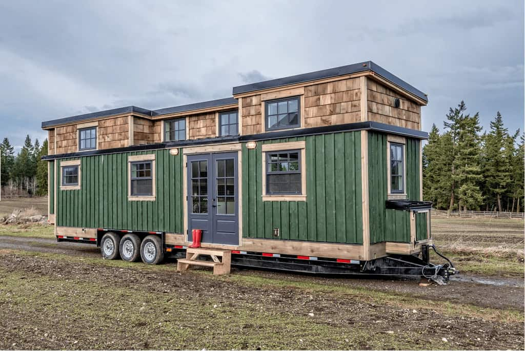 A container home painted with its exterior painted in green.